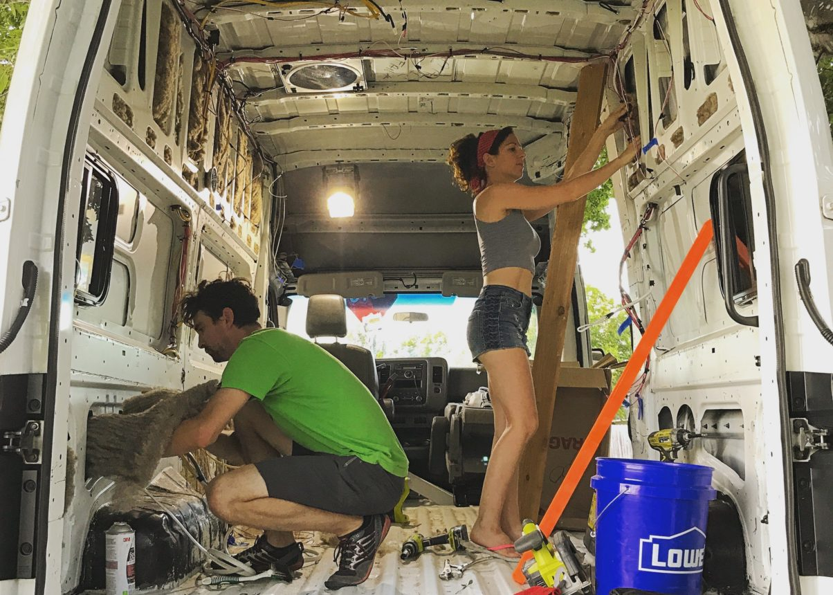 couple installing wool insulation sustainable camper van